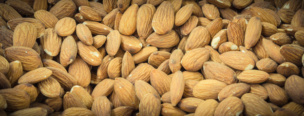 Background pile of organic dried almond bulk sale at local market in America. Full frame view of raw almonds, healthy nut