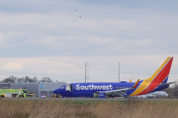 Canda Geese fly overhead as emergency personnel monitor the damaged engine of Southwest Airlines Flight 1380, which diverted to the Philadelphia International Airport this morning, in Philadelphia, Pennsylvania