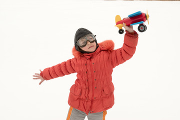 A funny girl in flying glasses and pilot's helmet and red ski jacket. Kid plays with toy plane, introducing himself as pilot. Girl is happy to spend his holidays in village. Winter Joys and Snow