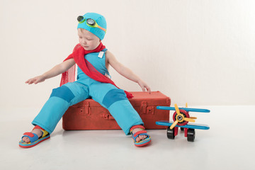 Funny boy in blue overalls and hat, wearing a red scarf and glasses for swimming, sits on vintage suitcase with an airplane model and dreams of adventures. Concept of romance of travel and discovery