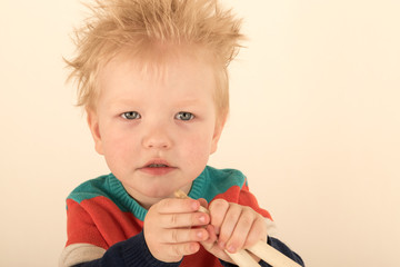 Happy Caucasian  blonde with microphone. Drummer play on a new drum kit. Parents bought a drum box for training. Child in bright clothes with new chopsticks in hands happy at home. Bright emotions