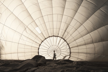View to inside big space of white expanding hot air balloon (atmosphere balloon) during preparation before flight with shadow of worker man holding center during blowing