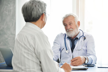 Senior male Doctor is talking with Asian male patient.