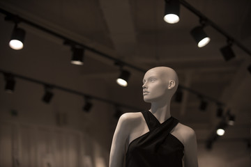 Mannequin in fashionable clothes on grey background with stylish chandeliers. Shopping and boutique concept. Shining fashionable luxury doll. White plastic mannequin with black dress.