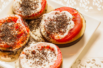 Slices of eggplant and tomatoes baked with goat cheese and chia seeds on white plate on old wooden table,top view, overhead, flat lay