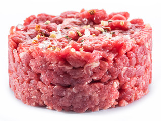 Ground cutlet or raw hamburger with seasonings on white background. Close-up.