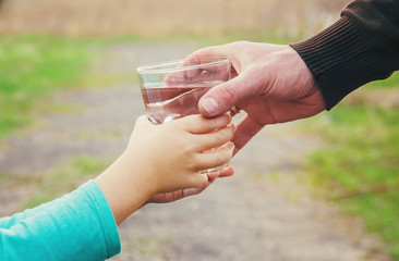 The father gives the child a glass of water. Selective focus.