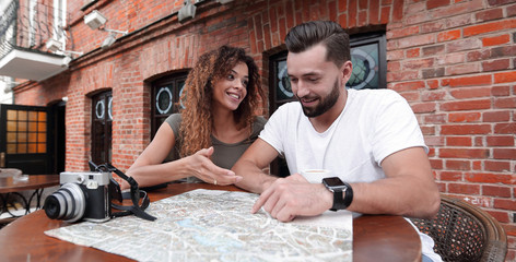 Couple in an outdoor cafe using map and planning itinerary