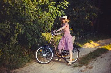 Beautiful girl wearing a nice pink dress having fun in a park with a bicycle holding a beautiful basket with flowers. Vintage landscapes. Pretty blonde with retro look, bicycle and basket with flowers