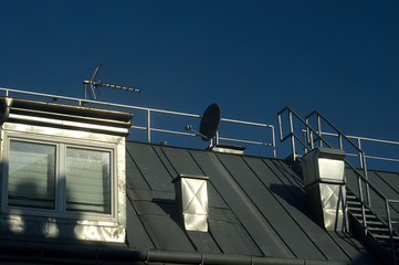 Sunny roof with attic, chimneys and TV antennas