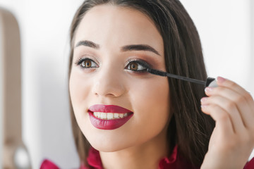 Portrait of beautiful woman applying makeup on blurred background