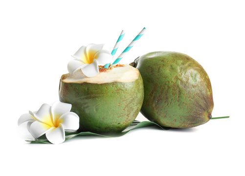 Fresh green coconuts with drinking straws and flowers on white background