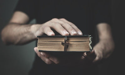 Caucasian man holding a holy bible.