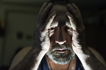 Close up of sad man in dark room. Depression and anxiety disorder concept.