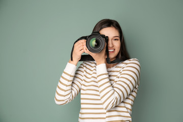 Young female photographer with camera on grey background