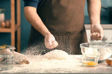 Man sprinkling flour over dough on table in kitchen