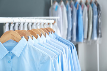 Rack with clean clothes on hangers after dry-cleaning indoors