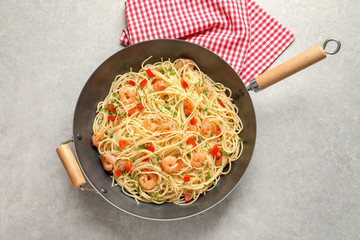 Frying pan with spaghetti and shrimps on light background, top view