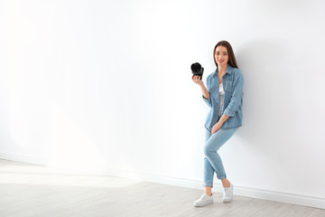 Female photographer with camera near light wall indoors