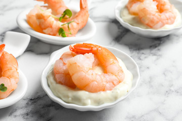 Bowls with boiled shrimps and sauce on light background