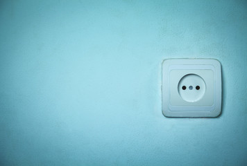 Electric socket on a blue wall.