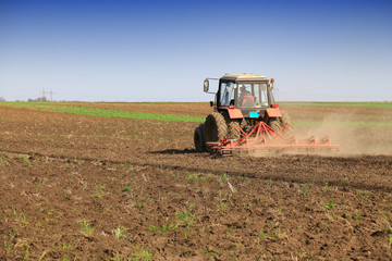 Tractor fertilize field before seeding