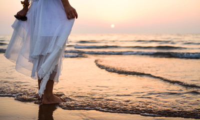 Girl walking on the beach wearing white dress