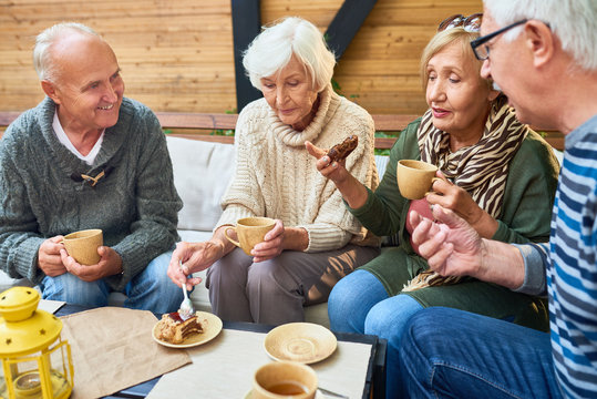 Group of modern seniors enjoying time together drinking tea in outdoor cafe and sharing life stories in retirement