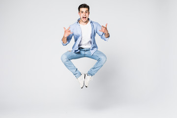 happiness, freedom, movement and people concept - smiling young man jumping in air isolated on white