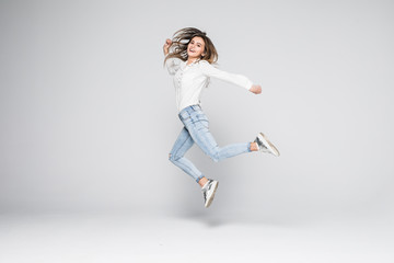 Portrait of a cheerful cute woman jumping isolated on a white background