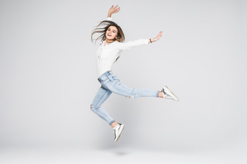 Full length portrait of a cheerful woman jumping isolated on a white background Wall mural
