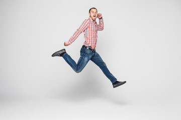 Vertical image of happy man in shirt and jeans which jumping in studio over white background