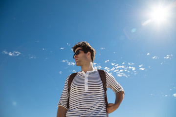 Young man with backpack looking away from the sun against blue sky