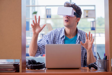 Young man playing computer game with virtual reality glasses
