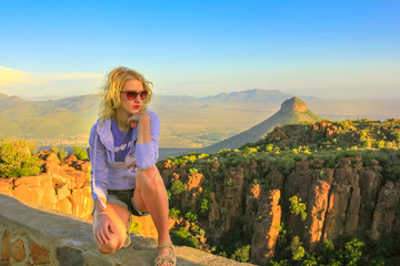 Young tourist sitting on the rocks at sunset after trekking at Valley of Desolation near Graaff-Reinet, South Africa. Blonde woman enjoying aerial views of Camdeboo National Park, Karoo, Eastern Cape.