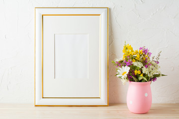 Gold decorated frame mockup with wildflowers in pink vase