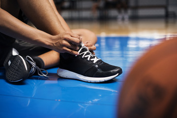 African American teenage boy tying his shoe laces on a basketball court