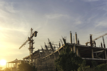 Tower crane with building structure under construction  with sunset
