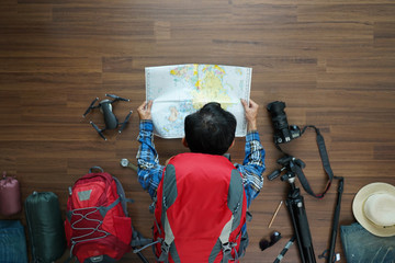 Overhead view of traveler man plan and backpack planning vacation travel idea concept trip with map. Top view.