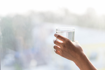 Hand holding glass of water with blur light in the morning background, healthy concept