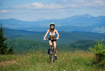 Active girl biker riding on yellow mountain bike on a grass, wearing helmet, on sunny day. Mountains, blue sky on the blurred background. Outdoor sport activity