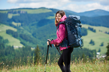 Portrait of beautiful sporty woman hiker with blue backpack and trekking sticks, hiking in the mountains, smiling to the camera, enjoying summer day in the mountains. Concept of active lifestyle