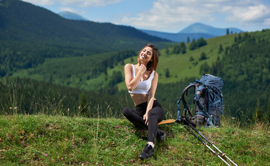 Pretty girl tourist with backpack and trekking sticks sitting with closed eyes, resting after hiking on the top of a hill, enjoying summer day in the mountains. Concept of active lifestyle