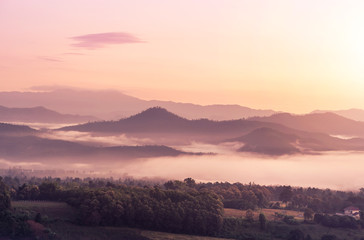 landscape view of sunrise on high angle view with white fog in early morning over rainforest mountain