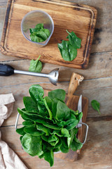 Top view fresh bunch of spinach leaves with blender for cooking sauce on wooden table