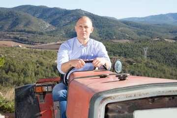 Male owner of vineyard driving tractor