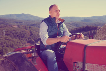 Confident  male owner of vineyard driving tractor outdoors in sunny day