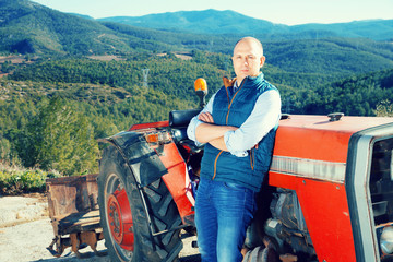 Portrait of adult male farmer near tractor on background with la