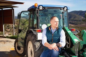 Confident male owner of vineyard posing near tractor outdoors in sunny day