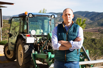 Confident male owner of vineyard posing near tractor outdoors in